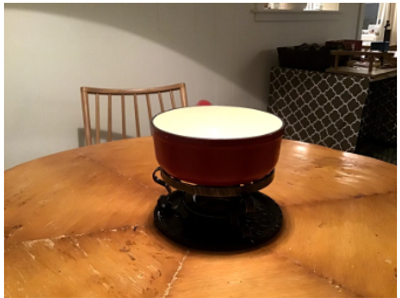 Fondue Pot sitting on table.