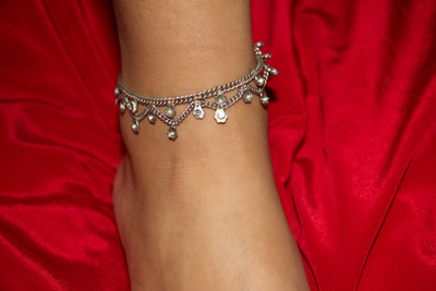 This is a rusty silver anklet which has a few white stones and some are clearly missing.