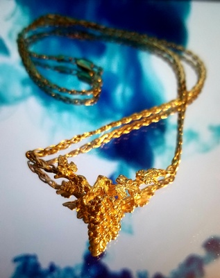 Photo of necklace placed upon a glass.