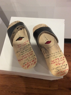 A wooden clog , with proverbs Arabic