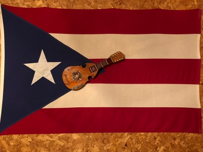 On top of the Puerto Rican flag that Lily and Pedro have in their living room, is a small guitar called a Cuatro that is native to Latin America.
