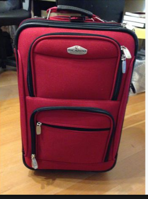 Red suitcase with multiple shiny zippers